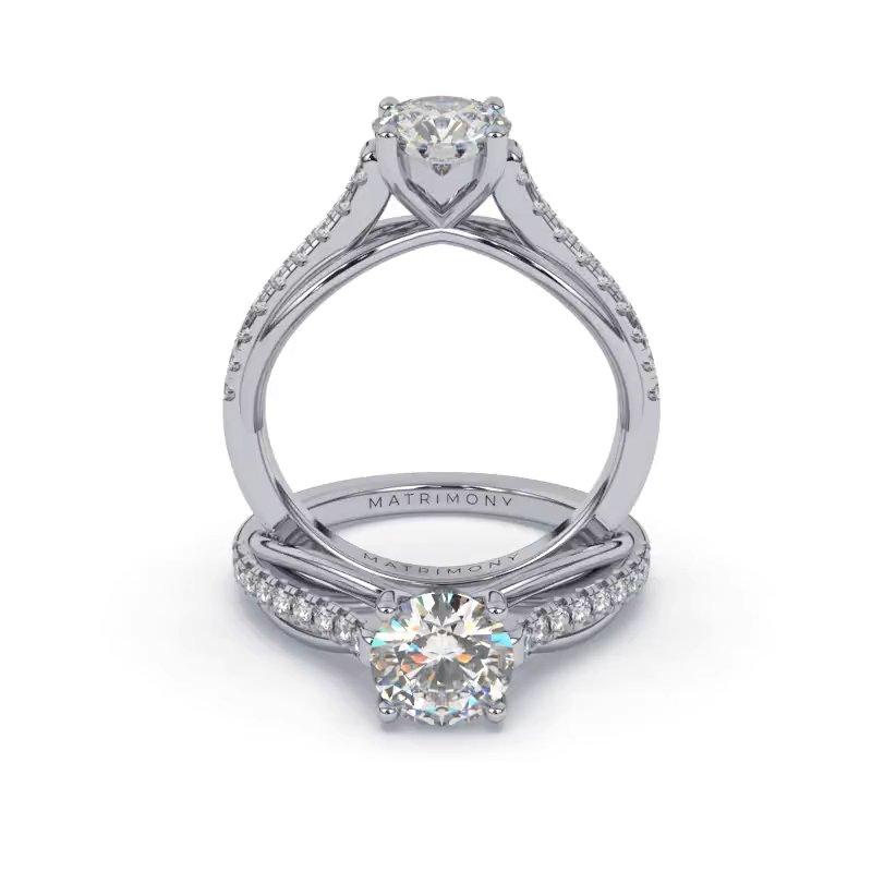 Hermoso anillo de compromiso con piedras laterales y diamante redondo. Este modelo se encuentra disponible con piedras de zirconia o diamante, además de poderse crear con oro de 9k, 14k, 18k y platino.